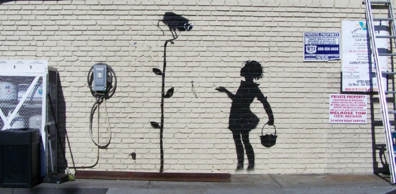 """This undated publicity photo released by Julien's Auctions shows the Banksy graffiti mural entitled, """"Flower Girl,"""" which formerly occupied a gas station in Los Angeles. The mural headlines Julien's Auctions """"Street Art"""" auction to take place Thursday, December 5, 2013, in Beverly Hills, Calif. (AP Photo/Julien's Auctions)"""