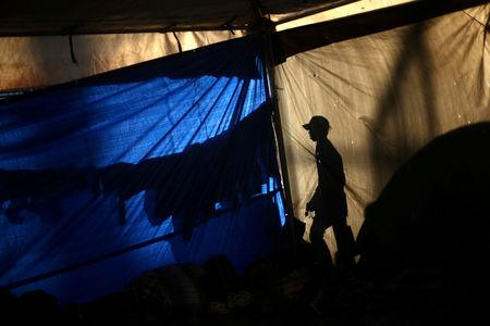 A migrant, part of a caravan of thousands traveling from Central America en route to the United States, is pictured inside a temporary shelter in Tijuana