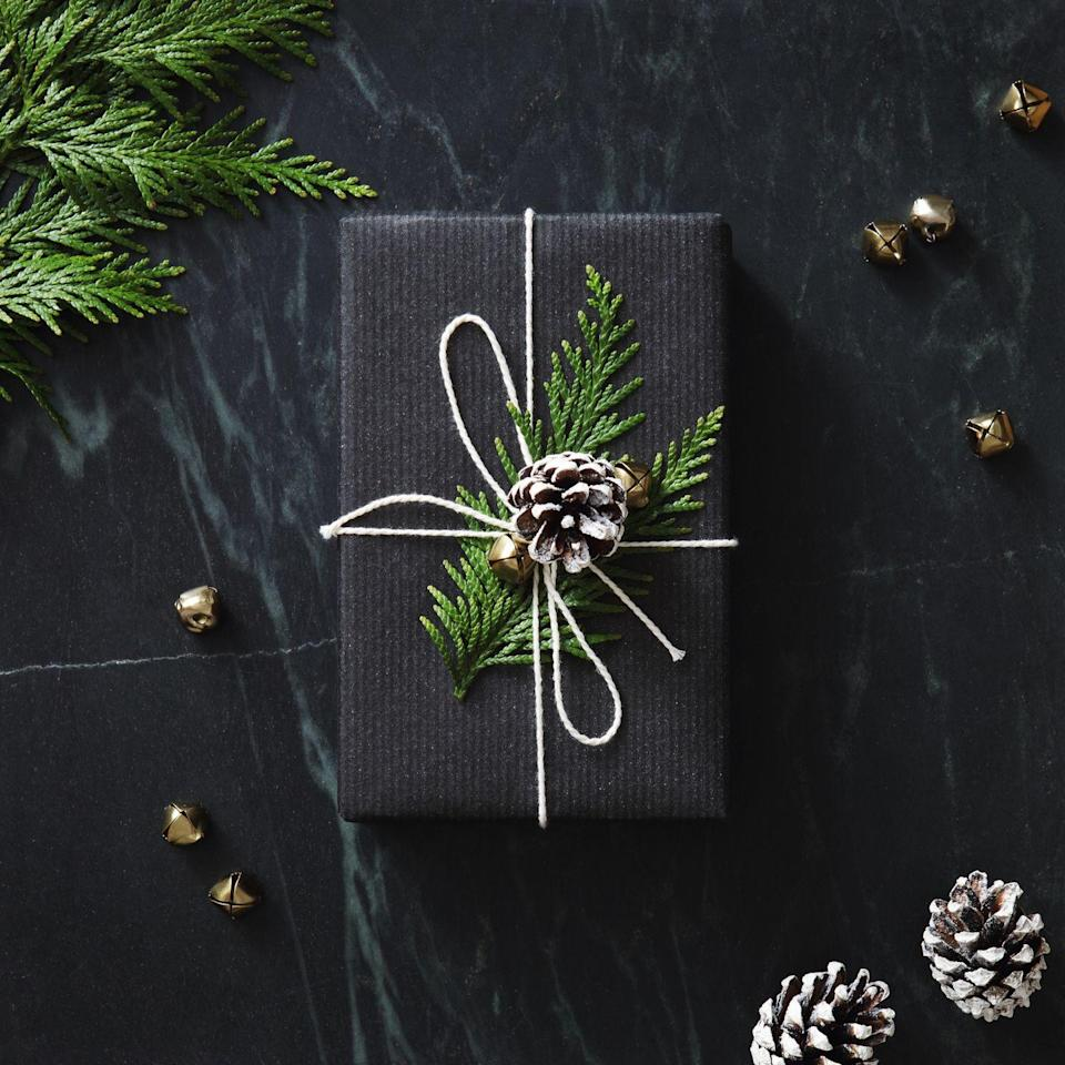 """<p>For Pinterest-worthy packaging, opt for dramatic black paper, then tie it all together with white yarn and natural elements like an evergreen sprig and a """"snow-covered"""" pinecone that works for Christmas or any winter birthday.</p><p><a class=""""link rapid-noclick-resp"""" href=""""https://www.amazon.com/BeautyMood-Natural-Christmas-Ornaments-Decorations/dp/B07M83DBPN?tag=syn-yahoo-20&ascsubtag=%5Bartid%7C10072.g.34015639%5Bsrc%7Cyahoo-us"""" rel=""""nofollow noopener"""" target=""""_blank"""" data-ylk=""""slk:SHOP PINECONES"""">SHOP PINECONES</a></p>"""