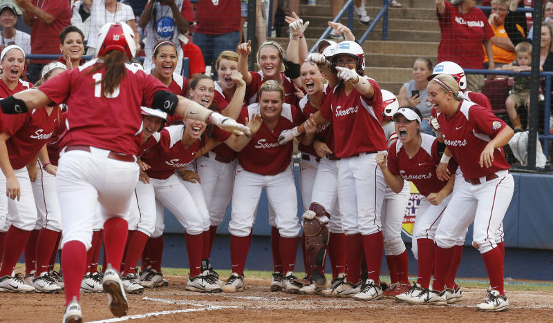 The Oklahoma team waits at home plate for teammate Keilani Ricketts (10) following her home run against Tennessee in the third inning of the second game of the best of three Women's College World Series NCAA softball championship series in Oklahoma City, Tuesday, June 4, 2013. (AP Photo/Sue Ogrocki)