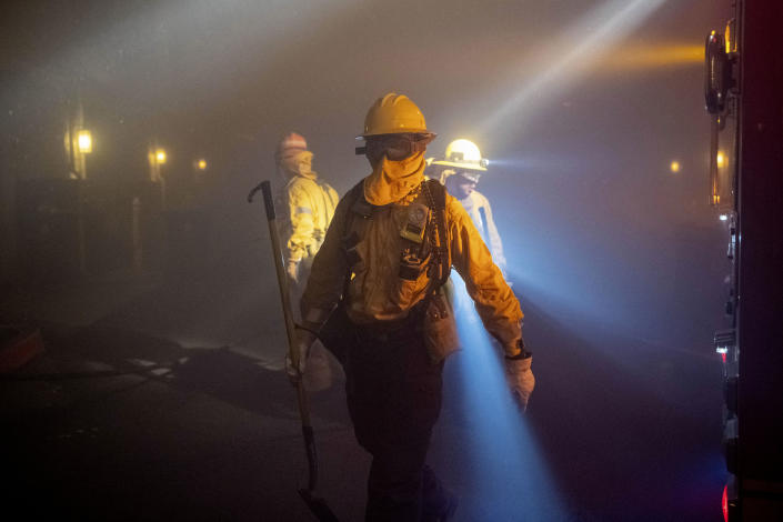 In this Thursday, Oct. 10, 2019 photo, firefighters check on homes in smoke from the Saddleridge fire in Sylmar, Calif. (Photo: Michael Owen Baker/AP)