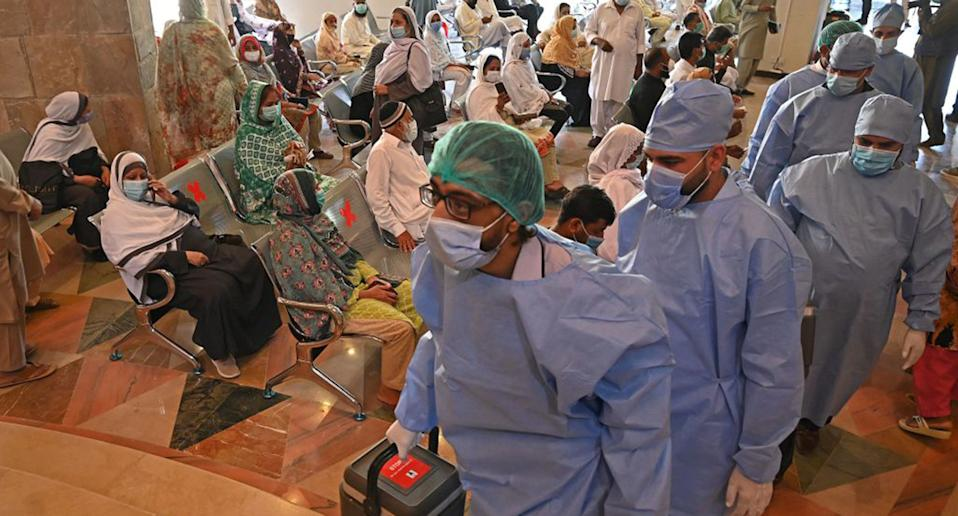 Health workers carrying vaccine carriers arrive as people wait for their turn to get inoculated with the jab of CanSino Biologics' Covid-19 coronavirus vaccine at a vaccination camp held in Islamabad on May 19, 2021.