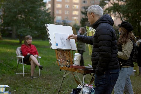 A man sketches a model in Central Park in New York City.