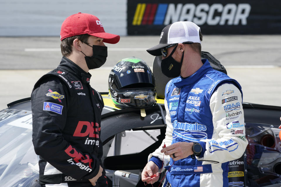 Cousins Harrison Burton, left, and Jeb Burton talk prior to the start of the rain delayed NASCAR Xfinity Series auto race at Martinsville Speedway in Martinsville, Va., Sunday, April 11, 2021. (AP Photo/Steve Helber)