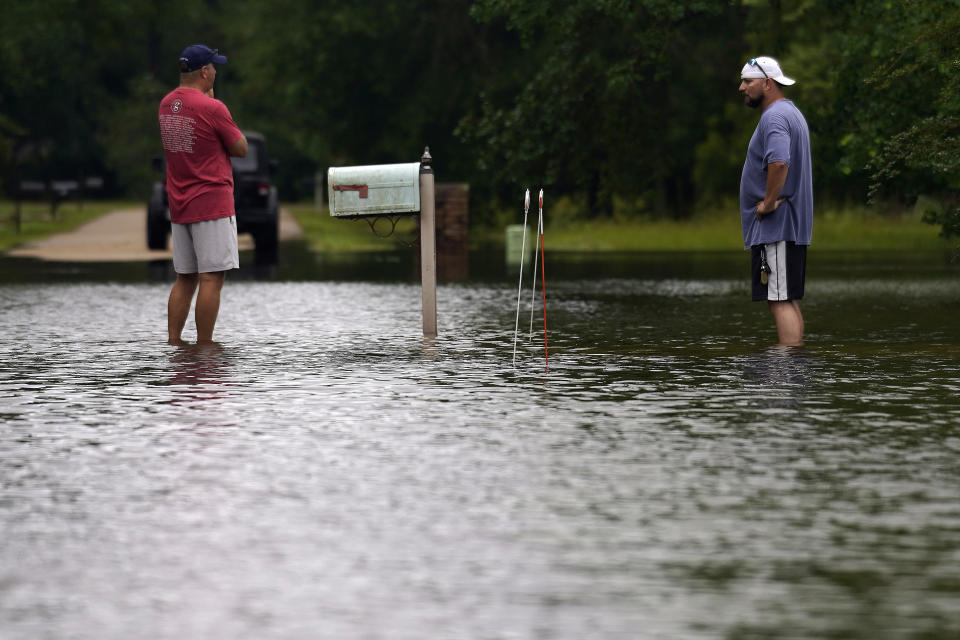 Danny Gonzales, right, stands in front of his flooded house with his neighbor Bob Neal, upset with power company trucks driving though the flooded neighborhood pushing water back into his home, after Tropical Storm Claudette passed through, in Slidell, La., Saturday, June 19, 2021. The National Hurricane Center declared Claudette organized enough to qualify as a named storm early Saturday, well after the storm's center of circulation had come ashore southwest of New Orleans. (AP Photo/Gerald Herbert)