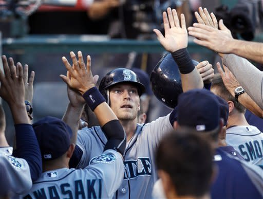 Seattle Mariners' Michael Saunders is congratulated in the dugout after scoring a run in the second inning of a baseball game against the Los Angeles Angels in Anaheim, Calif., on Wednesday, June 6, 2012. (AP Photo/Christine Cotter)