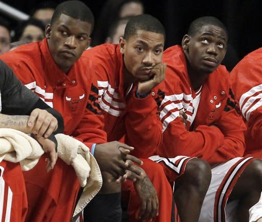 FILE - In this Feb. 18, 2012, file photo, Chicago Bulls guard Derrick Rose, center, sits on a bench between teammates Jimmy Butler, left, and Ronnie Brewer, during the second half of an NBA basketball game against the New Jersey Nets in Chicago. The Bulls enter the playoffs with the top overall seed for the second straight year and one big question mark heading into their first-round series against the Philadelphia 76ers. That involves their health, specifically Rose's. (AP Photo/Charles Rex Arbogast, File)