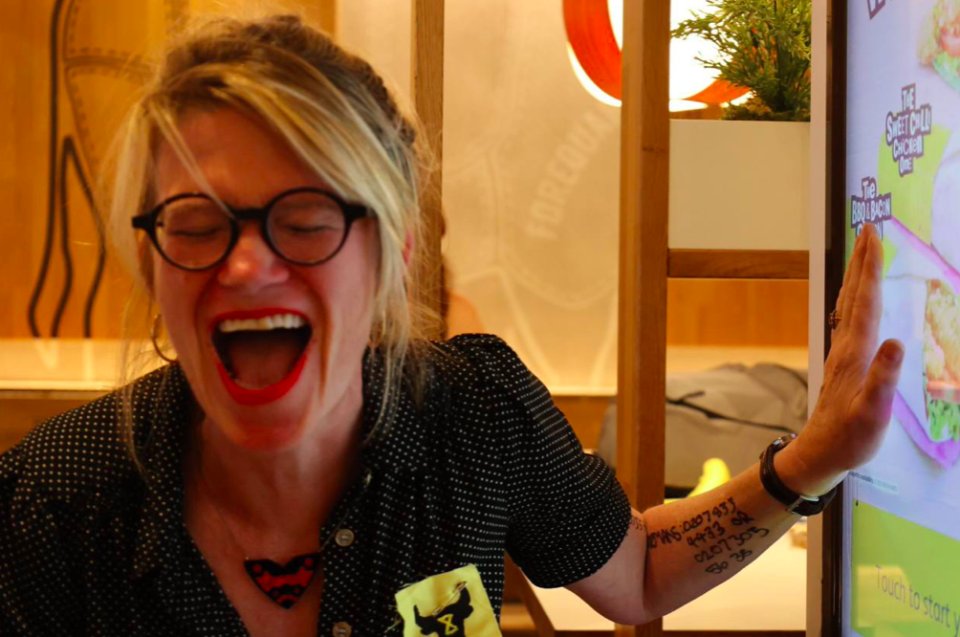 A protester reacts as she glues her hand to a screen inside McDonald's. (Twitter/Animal Rebellion)