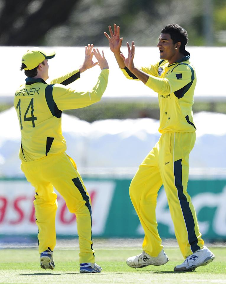 TOWNSVILLE, AUSTRALIA - AUGUST 11:  Gurinder Sandu  of Australia celebrates the wicket of Craig Overton with team mate Ashton Turner of Australia during the ICC U19 Cricket World Cup 2012 match between Australia and England at Tony Ireland Stadium on August 11, 2012 in Townsville, Australia.  (Photo by Ian Hitchcock-ICC/Getty Images)