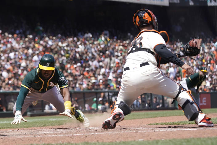 Oakland Athletics' Tony Kemp, left, slides into home to score against San Francisco Giants catcher Buster Posey during the sixth inning of a baseball game in San Francisco, Sunday, June 27, 2021. (AP Photo/Jeff Chiu)