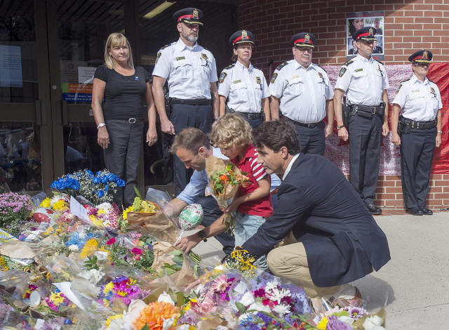 <p>Prime Minister Justin Trudeau, accompanied by his four-year-old son Hadrien and Fredericton MP Matt DeCourcey, left, places flowers outside the police station in Fredericton on Sunday, Aug. 12, 2018. Two city police officers were among four people who died in a shooting in a residential area on the city's north side. (Photo from The Canadian Press/Andrew Vaughan </p>