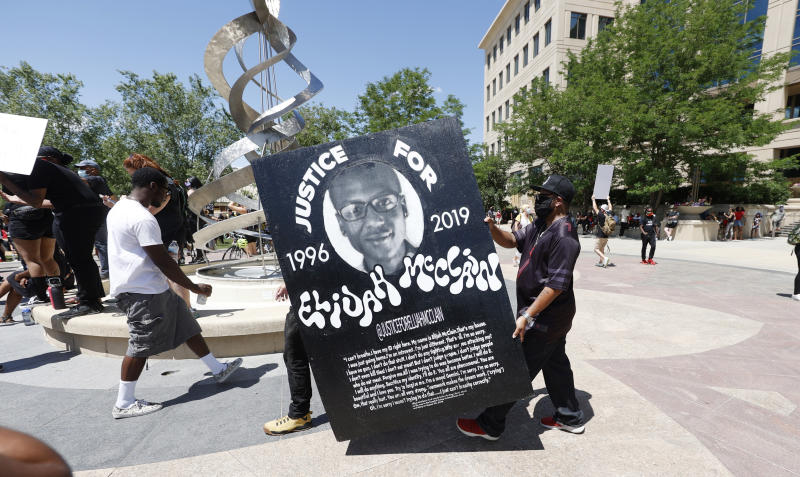 """FILE - In this June 27, 2020, file photo, demonstrators carry a giant placard during a rally and march over the death of 23-year-old Elijah McClain outside the police department in Aurora, Colo. Multiple suburban Denver police officers have been placed on paid administrative leave amid an investigation into photos of them related to the case of a Black man who died last summer after he was stopped and restrained, police said Monday, June 29, 2020. The interim police chief of the city of Aurora, Vanessa Wilson, said in a statement that the suspended officers were """"depicted in photographs near the site where Elijah McClain died."""" But her statement did not provide more details about what the images show. (AP Photo/David Zalubowski, File)"""