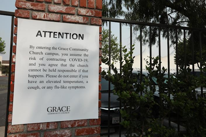 A sign on the back gate of the Grace Community Church states that all visitors assume the risk of contracting COVID-19.