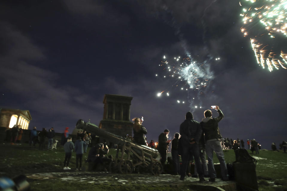 People on Calton Hill watch fireworks in Edinburgh as people are urged to avoid Hogmanay celebrations in the midst of tough coronavirus restrictions Thursday Dec. 31, 2020. (Andrew Milligan/PA via AP)