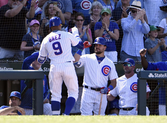 Chicago Cubs' Javier Baez (9) is greeted by Kyle Schwarber, center, after hitting a home run against the Cincinnati Reds during the seventh inning of a baseball game Saturday, July 7, 2018, in Chicago. (AP Photo/David Banks)
