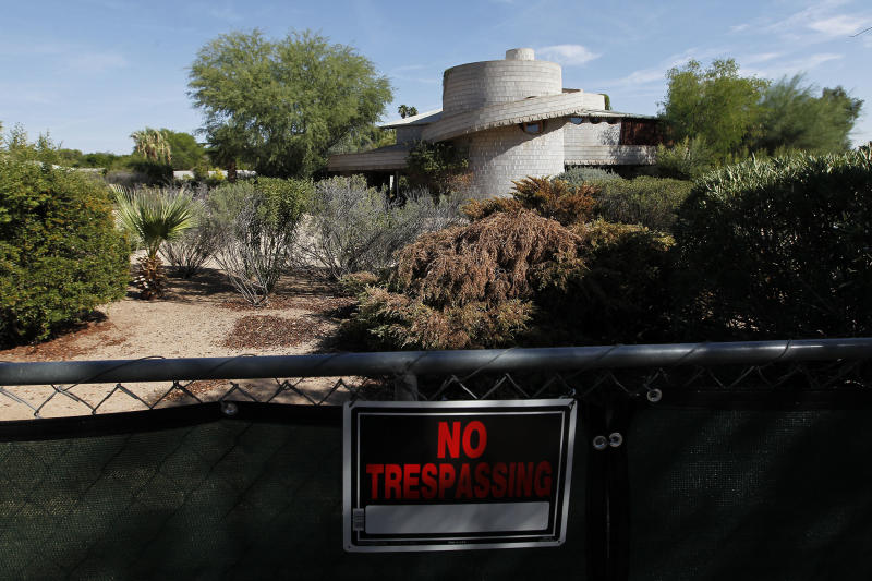 """A """"No Trespassing"""" sign hangs on a fence outside a 1952 Frank Lloyd Wright-designed home in the Arcadia neighborhood of Phoenix, Wednesday, Oct. 3, 2012. The city of Phoenix and a developer who was poised to demolish the home have reached an agreement that will put any work on hold while a search continues for a buyer, a city official confirmed Wednesday. (AP Photo/Ross D. Franklin)"""