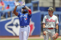 Toronto Blue Jays' Vladimir Guerrero Jr., left, celebrates his double as Philadelphia Phillies shortstop Nick Maton reacts during the second inning of a baseball game Sunday, May 16, 2021, in Dunedin, Fla. (AP Photo/Mike Carlson)