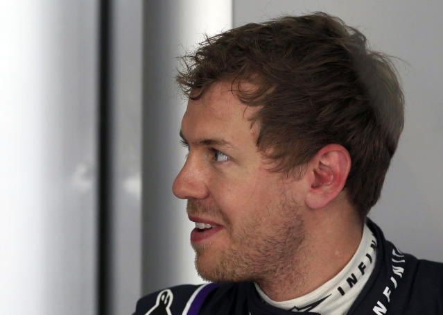 Red Bull driver Sebastian Vettel of Germany talks to a crew member in his team garage during the first practice session for Sunday's Malaysian Formula One Grand Prix at Sepang International Circuit in Sepang, Malaysia, Friday, March 28, 2014. (AP Photo/Lai Seng Sin)