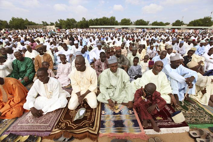 """Nigeria Muslim men and boys, offer their prayers during Eid al-Fitr, at Ramat square in Maiduguri, Nigeria, Thursday, Aug. 8, 2013. Nigerians in the birthplace of an Islamic uprising gripping the northeast Thursday celebrated the Muslim holy day of Eid al-Fitr with devout prayers and a joyful show of adulation for their king that attracted more than 10,000 people. It was the first durbar in three years in the city of Maiduguri and the joy that it could take place _ albeit amid massive security _ was heard in the cries of ululating women, screams of delight from children and men chanting """"Long live the king!"""" (AP Photo/Sunday Alamba)"""