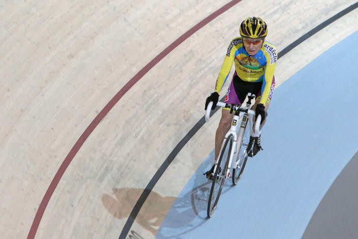French cyclist Robert Marchand, aged 102, cycles in a bid to beat his record for distance cycled in one hour, at the velodrome of Saint-Quentin en Yvelines, outside Paris, Friday, Jan. 31, 2014. The 102-year-old broke his own world record in the over-100s category Friday, riding 26.927 kilometers (16.7 miles) in one hour, more than 2.5 kilometers better than his previous best time in the race against the clock two years ago. (AP Photo/Thibault Camus)