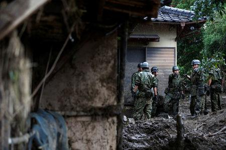 Japanese Self-Defense Force soldiers conduct search and rescue operation at a damaged house caused by a heavy rain in Asakura, Japan