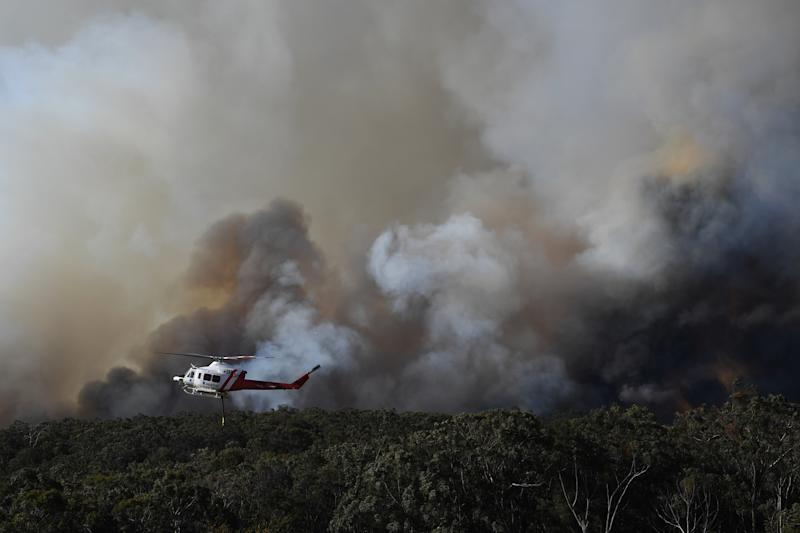 A stock image of a water bombing helicopter is seen battling fires in November.