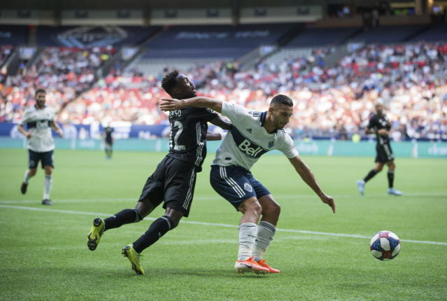 Sporting Kansas City's Gerso Fernandes, left, and Vancouver Whitecaps' Ali Adnan vie for the ball during the first half of an MLS soccer match Saturday, July 13, 2019, in Vancouver, British Columbia. (Darryl Dyck/The Canadian Press via AP)
