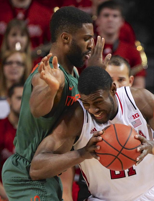 Nebraska's Leslee Smith, right, is guarded by Miami's Raphael Akpejiori in the first half of an NCAA college basketball game in Lincoln, Neb., Wednesday, Dec. 4, 2013. (AP Photo/Nati Harnik)