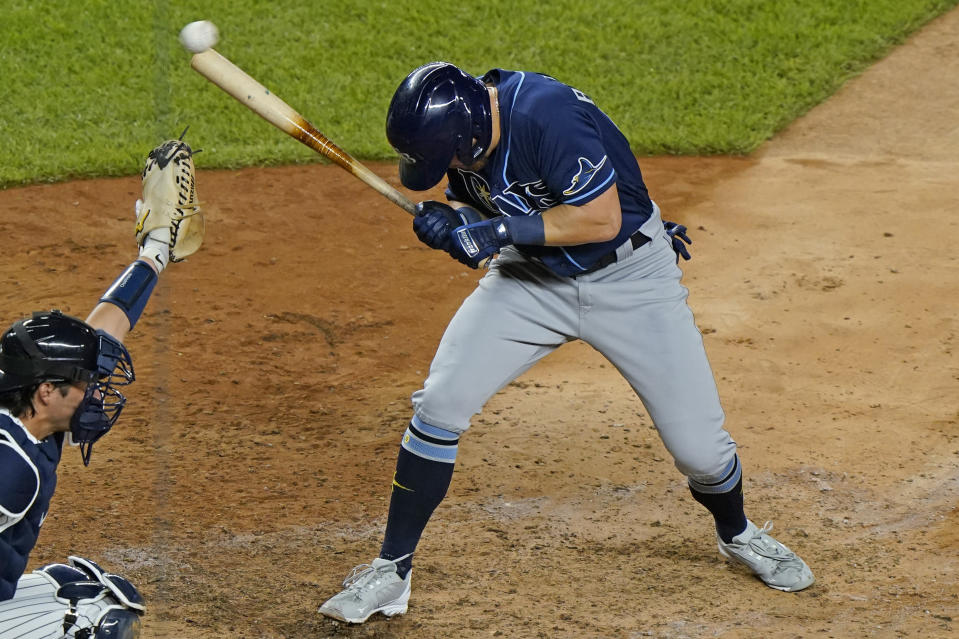 """FILE - In this Sept. 1, 2020, file photo, Tampa Bay Rays pinch-hitter Michael Brosseau ducks away from a pitch from New York Yankees reliever Aroldis Chapman during the ninth inning of a baseball game at Yankee Stadium in New York, as catcher Kyle Higashioga reaches for the ball. The Rays wear blue T-shirts with four horses lined up behind a fence, a reference to Tampa Bay manager Kevin Cash declaring """"I've got a whole damn stable full of guys that throw 98 miles an hour"""" in response to Aroldis Chapman throwing near the Mike Brosseau's head on Sept. 1.(AP Photo/Kathy Willens, File)"""
