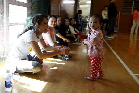 A 1-year-old Cambodian girl (R) and Cambodian residents in Japan cheer on their volleyball team during Asia Sports Festa in Yokohama, south of Tokyo, Japan, October 25, 2015. REUTERS/Yuya Shino/Files