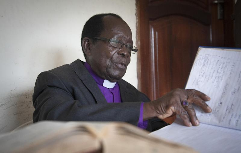 In this photo taken Sunday, March 16, 2014, Rev. Christopher Senyonjo, 82, gives a sermon on human sexuality at his makeshift church, the size of a small office, in Kampala, Uganda. Dressed in a purple shirt and white collar that highlight his Anglican faith, Bishop Senyonjo doesn't organize his Sunday evening prayers for homosexuals only, but his sermons attract many gays who are familiar with his sympathetic views in a country where other Christian preachers have led Uganda's anti-gay crusade. (AP Photo)