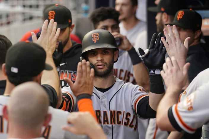 San Francisco Giants' Tommy La Stella (18) is congratulated in the dugout after hitting a home run during the first inning of the team's baseball game against the Atlanta Braves on Saturday, Aug. 28, 2021, in Atlanta. (AP Photo/John Bazemore)