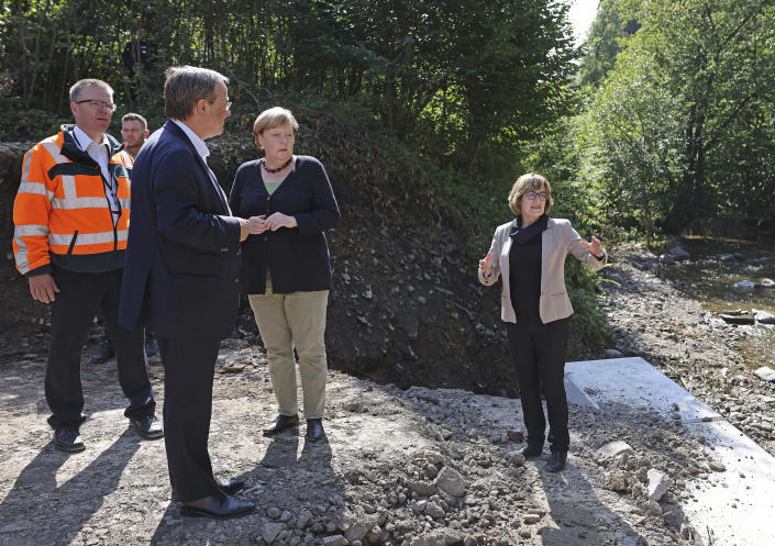 German Chancellor Angela Merkel, centre, and Armin Laschet, foreground left, candidate for chancellor of the CDU/CSU and chairman of the CDU, listen to Petra Beckefeld, right, from the road construction company Strassen, as they visit areas affected by flooding, in Hagen, Germany, Sunday, Sept. 5, 2021. (Oliver Berg/Pool Photo via AP