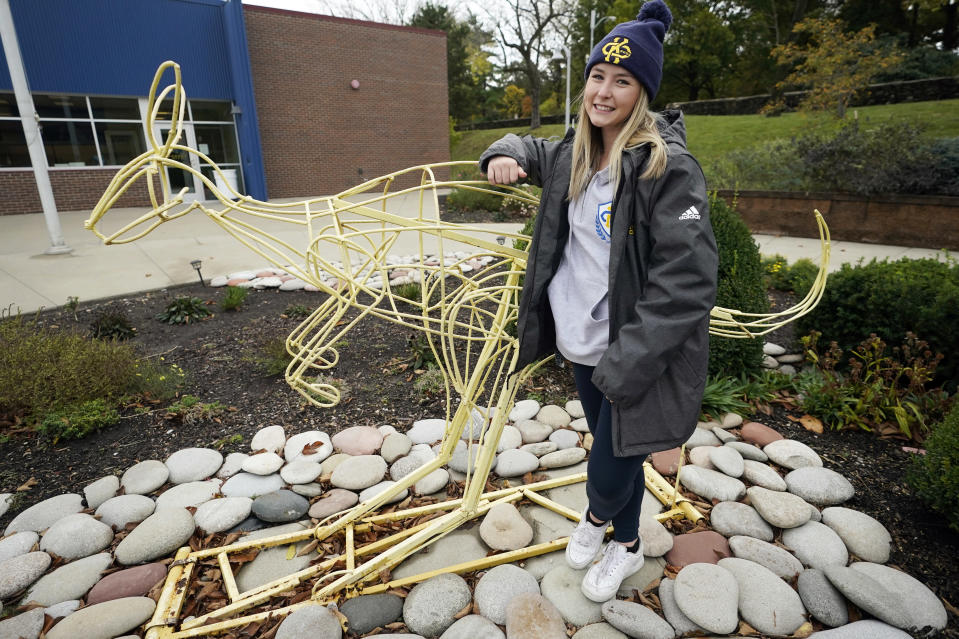 """Madison Zurmuehlen stands next to a sculpture of the University of Missouri-Kansas City's mascot outside the soccer facility in Kansas City, Mo., Friday, Oct. 23, 2020. Amid pandemic restrictions aimed at keeping students safe and healthy, colleges are scrambling to help them adjust. Zurmuehlen said daily practices, with masks, are """"the one thing I look forward to,"""" so it was tough when campus sports were canceled for two weeks after an outbreak among student athletes and staff. (AP Photo/Orlin Wagner)"""