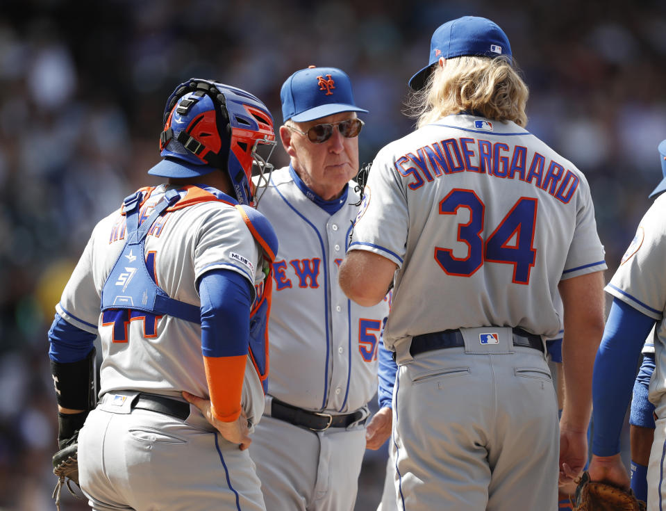 New York Mets interim pitching coach Phil Regan, center, confers with catcher Rene Rivera, left, and starting pitcher Noah Syndergaard after he walked Colorado Rockies' Ryan McMahon to load the bases for Nolan Arenado in the fifth inning of a baseball game Wednesday, Sept. 18, 2019, in Denver. (AP Photo/David Zalubowski)