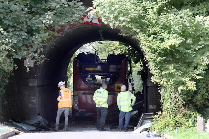 An engineer and police forensic vehicle examiners inspect the scene on Well House Lane in Winchester after three children were taken to hospital with serious injuries while 13 others suffered minor injuries after the school bus they were travelling in crashed into a railway bridge.
