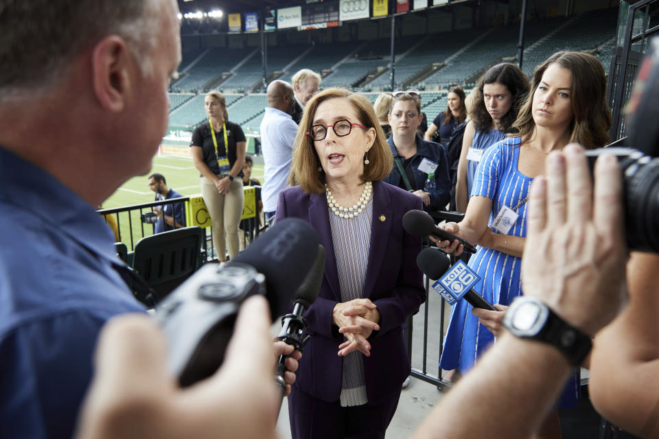 Oregon Governor Kate Brown talks talks with media after announcing the end of the state's COVID-19 restrictions in Portland, Ore., Wednesday, June 30, 2021. (AP Photo/Craig Mitchelldyer)