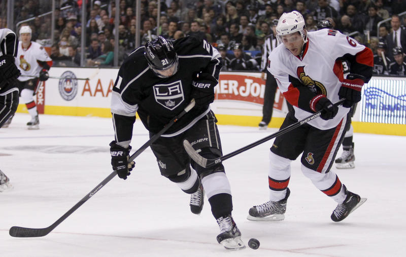 Los Angeles Kings right wing Matt Frattin, left, battles Ottawa Senators right wing Bobby Ryan (6) for the puck during the first period of their NHL hockey game on Wednesday, Oct. 9, 2013, in Los Angeles. (AP Photo/Alex Gallardo)