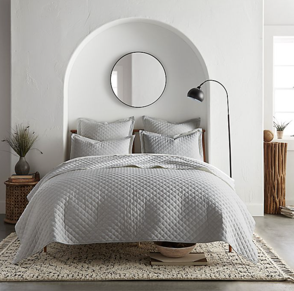 grey Linen/Cotton 3-Piece King Quilt Set next to white walls and circle mirror