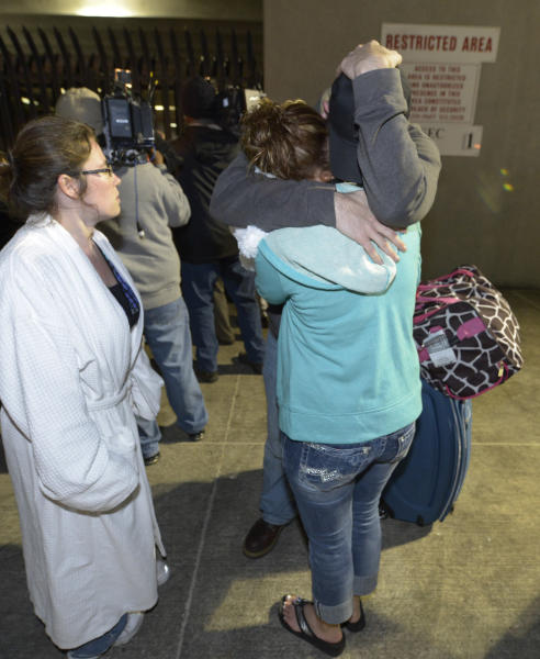 Passengers embrace after disembarking from the cruise ship Carnival Triumph in Mobile, Ala., Thursday, Feb. 14, 2013. The ship with more than 4,200 passengers and crew members has been idled for nearly a week in the Gulf of Mexico following an engine room fire. (AP Photo/John David Mercer)