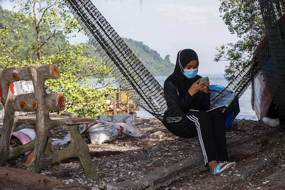 Nur Alea Soffiyyah Ahmad Hanif attends online classes in front of her house on Pulau Aman January 22, 2021. — Picture by Sayuti Zainudin