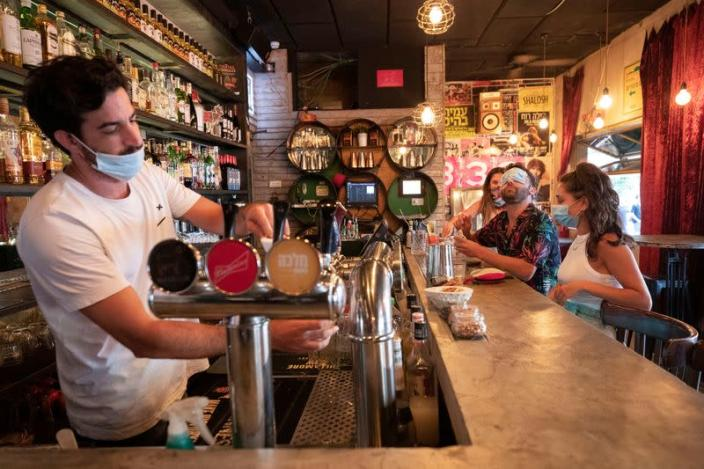 A bartender and customers wear face masks to fight the spread of the coronavirus disease (COVID-19) at a bar in Tel Aviv