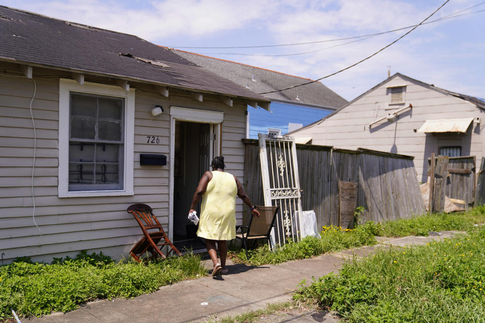 In the aftermath of Hurricane Ida, Lationa Kemp, 57, walks into her home, Saturday, Sept. 4, 2021, in the Lower Ninth Ward of New Orleans. (AP Photo/Matt Slocum)