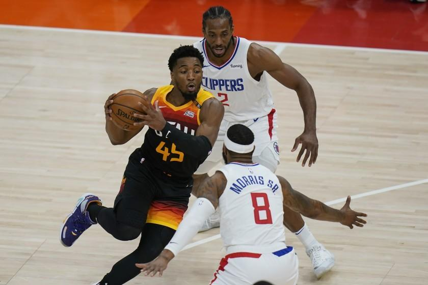 Los Angeles Clippers' Kawhi Leonard (2) and Marcus Morris Sr. (8) defend against Utah Jazz guard Donovan Mitchell (45) during the first half of Game 1 of a second-round NBA basketball playoff series Tuesday, June 8, 2021, in Salt Lake City. (AP Photo/Rick Bowmer)