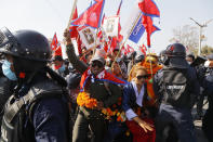 Pro-king supporters are stopped by riot police as they march demanding reinstating monarchy that was abolished more than a decade ago in Kathmandu, Nepal, Monday, Jan.11, 2021. Monday's protest was the latest anti-government protest against Prime Minister Khadga Prasad Oli who has been facing street demonstrations against him from a splinter faction of his own Communist party and more from opposition political groups for dissolving parliament. Nepal's centuries-old monarchy was abolished in 2008 by the parliament and replaced by a republic where the president was elected as the head of state. (AP Photo/Niranjan Shrestha)