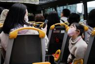 A child wearing a face mask poses for a picture as passengers enjoy an open-top sightseeing bus tour, operated by Hato Bus Co., as the tour service resumed after Japan's government lifted the coronavirus disease (COVID-19) state of emergency in the Tokyo