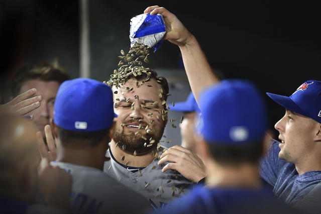 Toronto Blue Jays' Rowdy Tellez, center, has sunflower seeds poured over him in the dugout after hitting a grand slam against the Baltimore Orioles during the fifth inning of a baseball game Wednesday, June 12, 2019, in Baltimore. (AP Photo/Gail Burton)