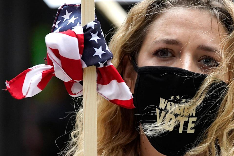 Lindsey Schwartz wears a mask with a message as she holds a sign during the Women's March in downtown Chicago, Saturday, Oct. 17, 2020.