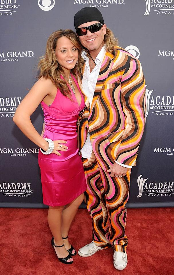 """Brooke Burrows and Ira Dean  Grade: F   Brooke Burrows' hot pink frock was fine, but she earned herself an F as well for allowing Former Trick Pony bassist Ira Dean to leave the house in this multi-colored nightmare of a suit. Rick Diamond/ACMA2011/<a href=""""http://www.gettyimages.com/"""" target=""""new"""">GettyImages.com</a> - April 3, 2011"""