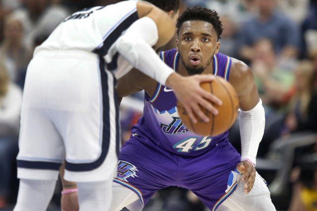Utah Jazz guard Donovan Mitchell (45) looks to defend against Memphis Grizzlies guard Tyus Jones (21) during the first half of an NBA basketball game Saturday, Dec. 7, 2019, in Salt Lake City. (AP Photo/George Frey)